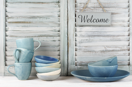 Simple rustic blue crockery against shabby wooden shutters: dish, bowls, mugs and Welcome plate. Stock Photo