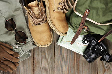 Travel accessories set on wooden background: old hiking leather boots, pants, backpack, map, gloves, vintage film camera and sunglasses. Top view point.