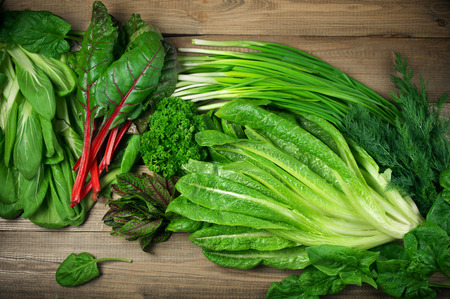 vitamina primavera de conjunto de diversas hortalizas de hoja verde en la mesa de madera rústica. Punto de vista superior. Foto de archivo