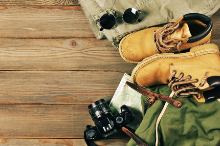 Travel accessories set on wooden background: old hiking leather boots, pants, backpack, map, vintage film camera and sunglasses. Top view point. Archivio Fotografico
