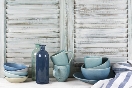 Simple rustic kitchen still life: handmade blue ceramic dish, bowls, mugs, glass bottles and towel against shabby wooden shutters.