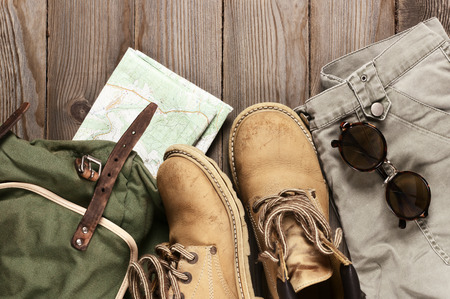 ramble: Travel accessories set on wooden background: old hiking leather boots, pants, backpack, map and sunglasses. Top view point. Stock Photo