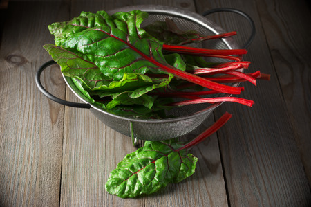 Fresh swiss chard leaves in wire basket on dark wooden table. Stock Photo