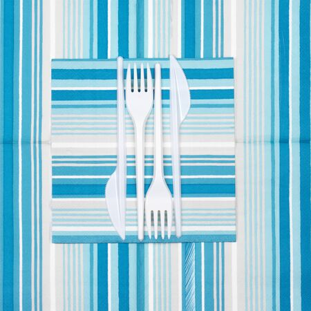 bar ware: Disposable cutlery: white plastic forks and knifes on blue striped paper napkins. Top view point. Stock Photo