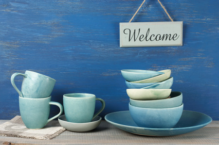 crockery: Handmade blue crockery set and Welcome plate against rustic blue painted wall.