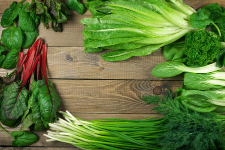 leafy: Spring vitamin set of various green leafy vegetables on rustic wooden table. Top view point. Stock Photo