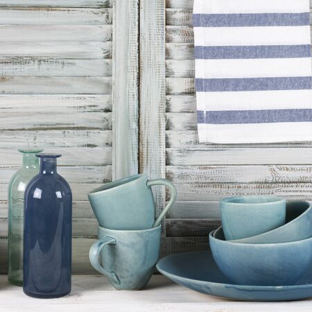 simple life: Simple rustic kitchen still life: handmade blue ceramic dish, bowls, mugs, glass bottles and towel against shabby wooden shutters.