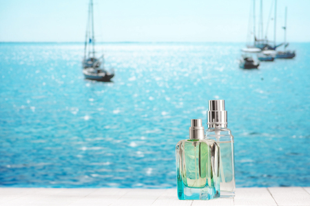 Two summer perfumes on white wooden table against defocused sunny sea with yachts.