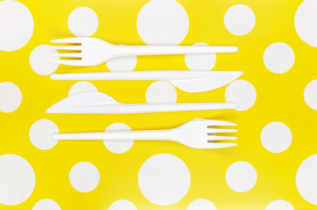 bar tool set: Disposable cutlery: white plastic forks and knifes on bright yellow polka dot background. Top view point.