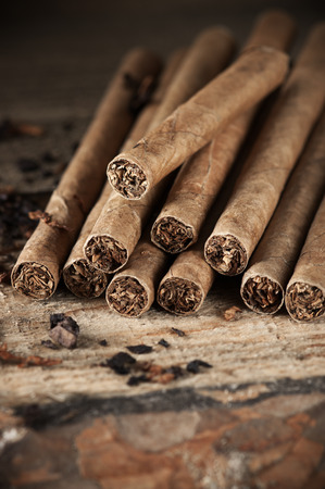 cigars: Aromatic cigars pile on vintage wood close-up. Stock Photo