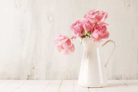 white table: Fresh tender pink garden roses in white jug on rustic white wooden background. Filtered retro stylized image.