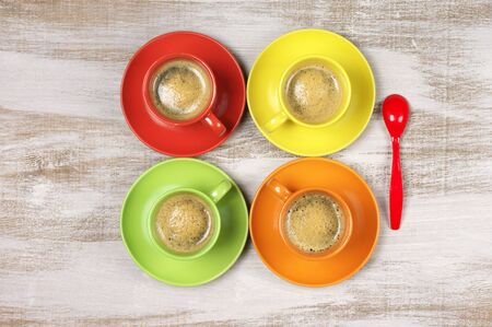 cup: Fresh espresso coffee in four cheerful bright colorful ceramic cups with saucers and red spoon on rustic wooden background. Top view point.