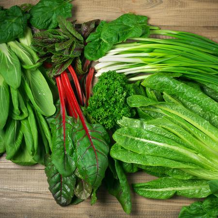 verduras verdes: vitamina primavera de conjunto de diversas hortalizas de hoja verde en la mesa de madera rústica. Punto de vista superior.