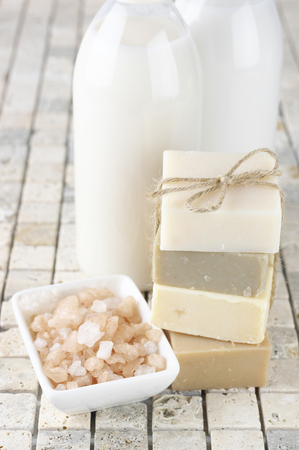 shower gel: Stack of various natural soaps, bath salt, shower gel and lotion on stone tile.