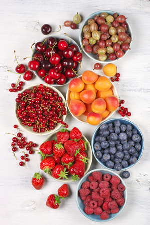 assortment: Various fresh fruits in bowls on white wooden background: strawberries, blueberries, raspberries, cherries, red currants, gooseberries and apricots. Top view point. Stock Photo