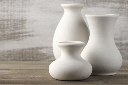 Three Empty White Unglazed Ceramic Vases On Wooden Table Against