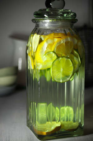 low glass: Fresh vitamin flavored fruit infused water with lime and lemon slices in glass jar on rustic wooden kitchen table. Low light.