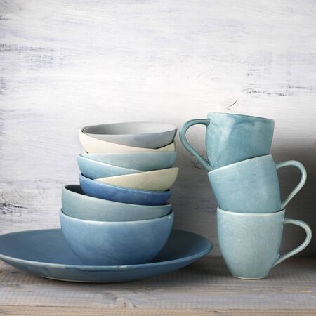 crockery: Simple rustic handmade blue crockery against wooden wall: dish, stack of bowls and mugs. Stock Photo