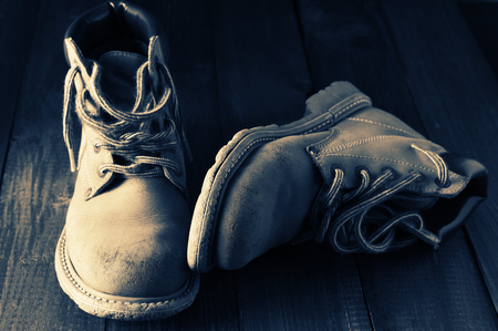 outworn: Old shabby leather hiking boots close-up on wooden background. Monochrome split toned image. Stock Photo