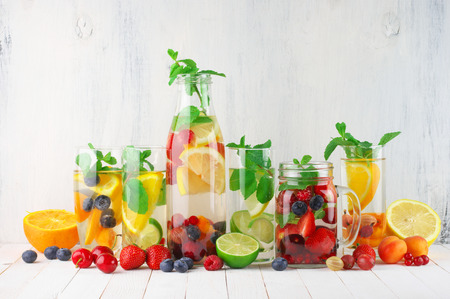 Various fresh vitamin flavored fruit infused water and fruits on white rustic wooden background.