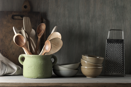 Kitchen utensil set in rough handmade ceramic pot, crockery, cutting boards, grater, towel on wood shelf against rustic wooden wall. Low light.