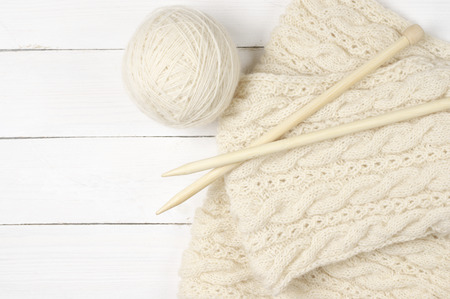 Natural woolen yarn and knitting with wood needles on white wooden background. Top view point. Stock Photo