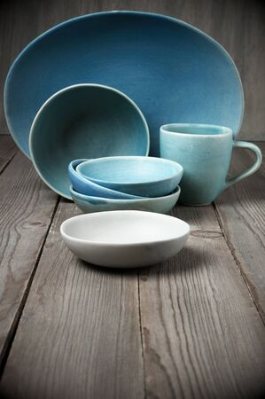 dishware: Rustic handmade blue ceramic dishware set on wooden table. Stock Photo