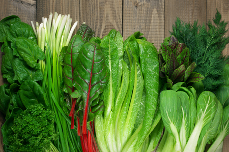 green leafy vegetables: Spring vitamin set of various green leafy vegetables on rustic wooden table. Top view point. Stock Photo