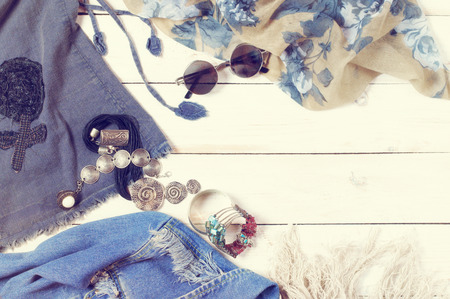 Set of woman clothes and accessories in boho style on white wood background. Top view point. Filtered toned image.