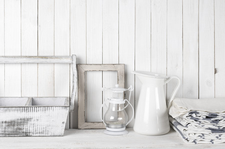towels wall: Rustic still life in white color: shabby wood box and photo frame, jug, lantern and towels against white wood wall.