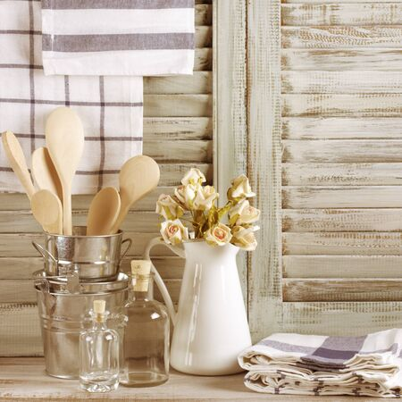 rustic kitchen: Rustic kitchen still life: white jug with roses bunch, galvanized buckets with wooden spoons, glass bottles and linen towels against vintage wooden shutters. Filtered toned image.