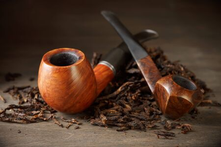 narcotic: Two wooden pipe and tobacco pile on vintage wood.
