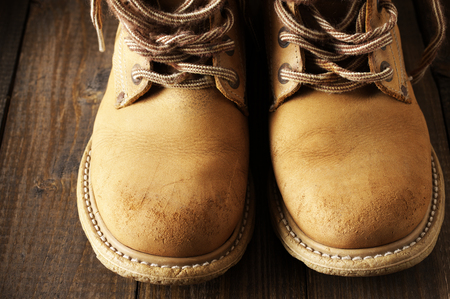 outworn: Old shabby leather hiking boots close-up on wooden background.