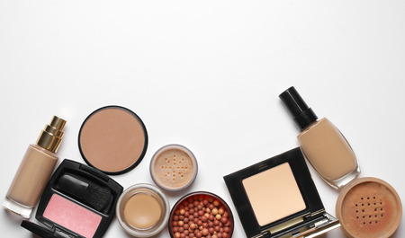 cosmetics products: Make-up cosmetics set of liquid and cream foundations, compact and loose powder in various tones, bronzing pearls and blush on white background. Top view point.