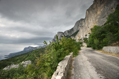 landslide: Old mountain road with landslide in overcast day. Crimea. Stock Photo