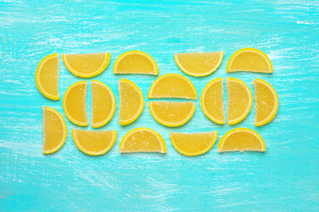 segmentar: Lemon segment shaped candied fruit jelly on turquoise colored wooden background. Top view point.