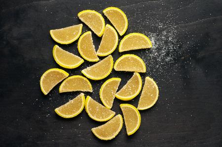 segmentar: segmento de limón en forma de jalea de frutas confitadas con azúcar en el fondo de madera negro. Punto de vista superior. Foto de archivo