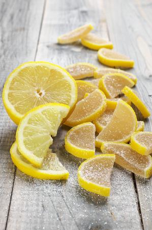 segmentar: Pila de segmento de limón en forma de jalea de frutas confitadas y rodajas de limón en el fondo de madera gris rústico.