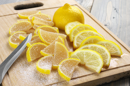 sweetstuff: Pile of lemon segment shaped candied fruit jelly and sliced lemon on wooden cutting board. Stock Photo
