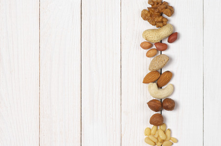 pine kernels: Variety of assorted nuts in row on white wood background with copy space. Top view point. Stock Photo