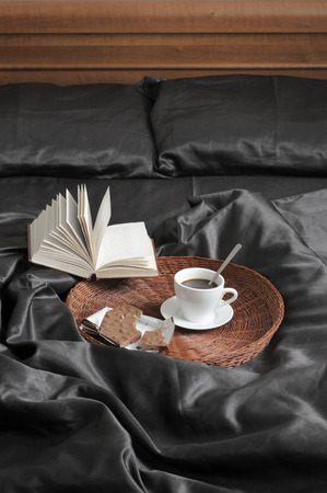 bedhead: Cup of coffee with milk chocolate on wicker tray and open book in bed with black satin linen and wooden bedhead. Text in book unreadable.