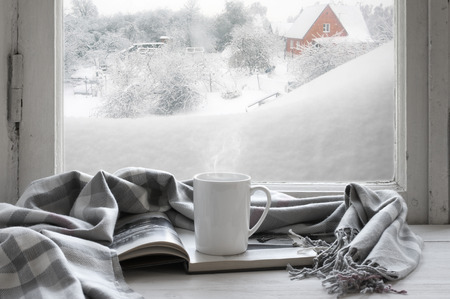 Cozy winter still life: mug of hot coffee and opened book with warm plaid on vintage windowsill of cottage against snow landscape with snowdrift from outside.