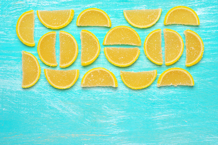 Lemon segment shaped candied fruit jelly on turquoise colored wooden background. Top view point.