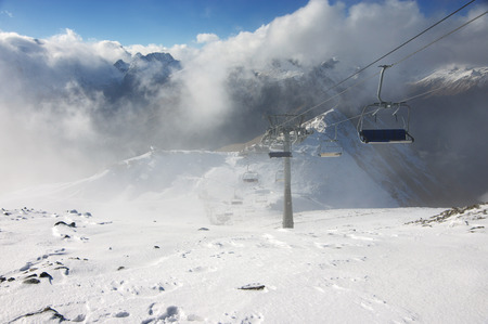 suspense: Cableway in snowy mountains with in mist and clouds. Ski resort, Dombay, Caucasus, Russia.