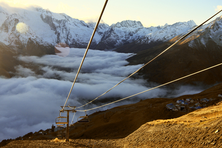 suspenso: Cableway in mountains over swirling fog at sunset. Wide angle view, lens flares.