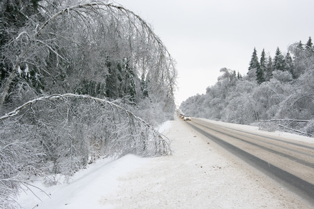 an icing: Snowy winter road among frozen forest after ice storm. Cold weather, snowfall,  slippery road. Moscow region. Stock Photo
