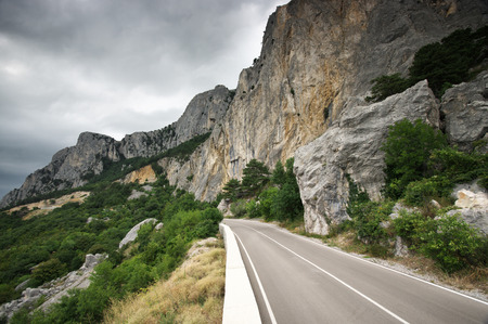 steep: Old mountain road with landslide in overcast day. Crimea. Stock Photo
