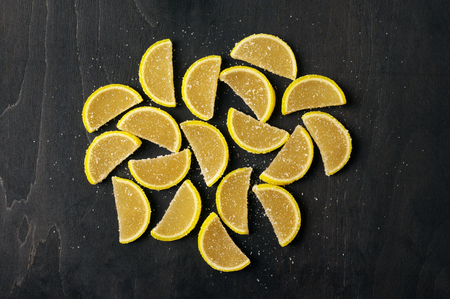 sweetstuff: Lemon segment shaped candied fruit jelly on black wooden background. Top view point. Stock Photo