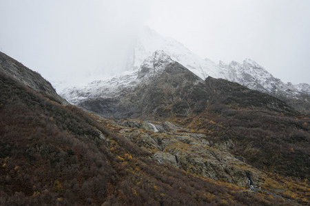severe weather: Minimalistic severe mountain landscape with snowy rocky peacks in fog at rainy weather. Dombay, Caucasus, Russia.