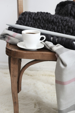 Leisure cozy still life: cup of coffee, super chunky knitting and blanket on vintage wooden chair in living room with shaggy carpet. Stock Photo